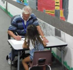 volunteer helping student with a lesson