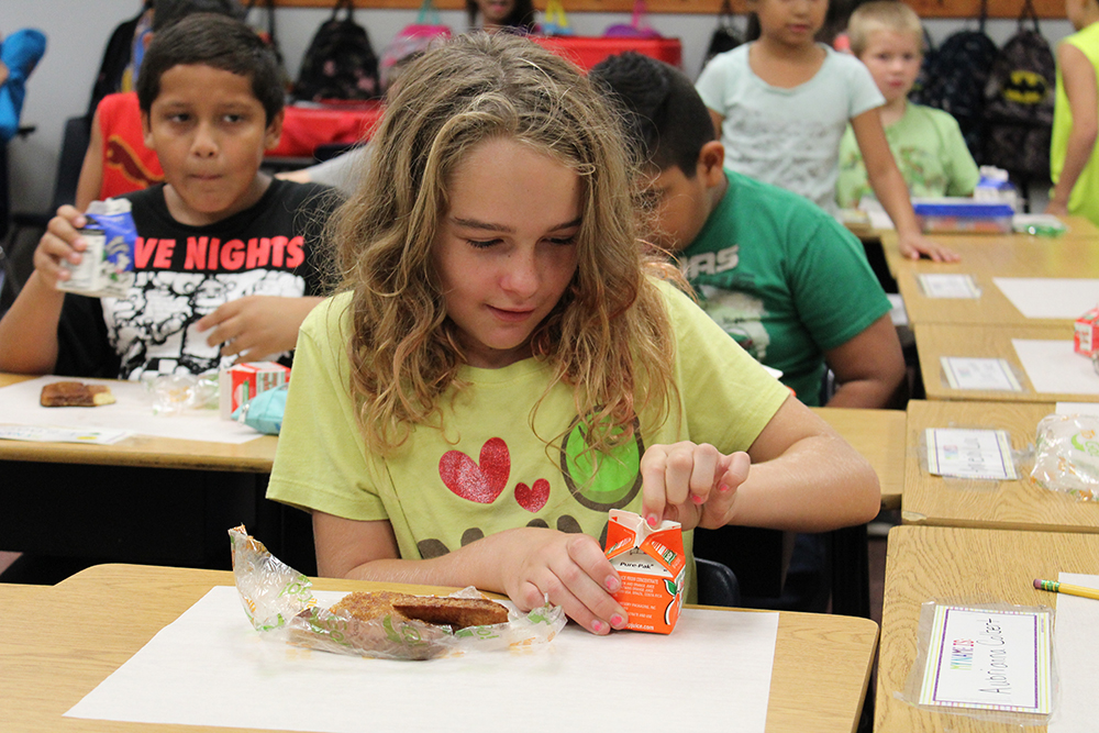 Girl opening her drink during breakfast in the classroom